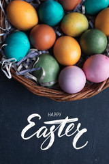 Happy Easter hand lettering inscription and colorful easter eggs in basket on black wooden background.