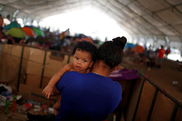 A Honduran mother holds her son at an improvised shelter while waiting for humanitarian visas to cross the country on their way to the United States, in Mapastepec