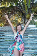 Cheerful woman in colorful apparel showing V sign with both hands and winking while standing near wooden fence on sunny day on caribbean beach, Tulum, Mexico