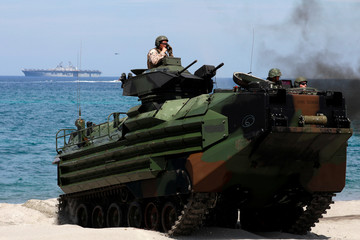 With the USS-Wasp in the background, U.S. Marines ride an amphibious assault vehicle during the amphibious landing exercises of the U.S.-Philippines war games promoting bilateral ties at a military camp in Zambales province