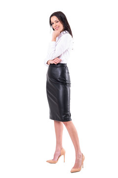 Playful flirty business woman winking and smiling at camera in white shirt and leather skirt. Full body isolated on white background.