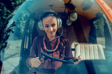 Joyful appealing woman wearing special headphones while being helicopter pilot Fototapete