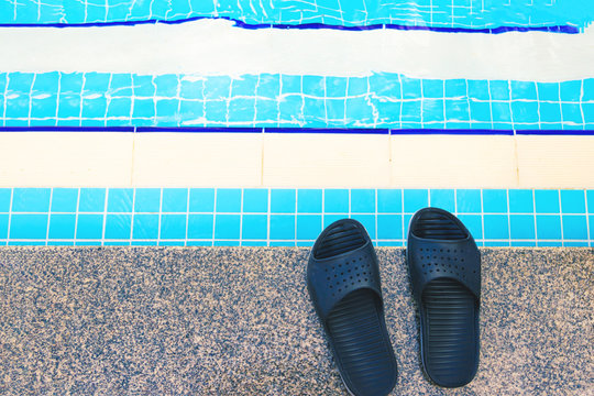 Summer background with slippers for the pool black color near the pool, steps for the descent into the pool.