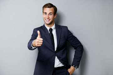 Portrait of happy smiling young businessman in confident black suit, showing thumbs up gesture, over grey background. Business success concept. Wall mural
