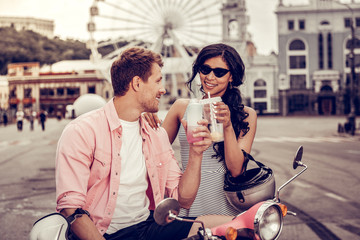 Joyful positive couple cheering with their drinks