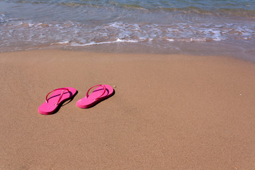 ff6769741 pink flip-flops on yellow sand at the water s edge on the beach