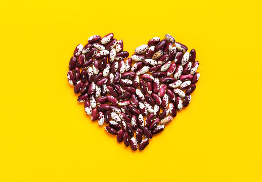 Heart made from dry uncooked red and white speckled beans on bright yellow background. Creative food art poster. Health plant based meatless diet wholefoods concept. Copy space