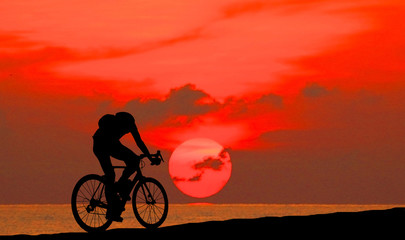 Silhouette man  and bike relaxing on blurry sky   background.
