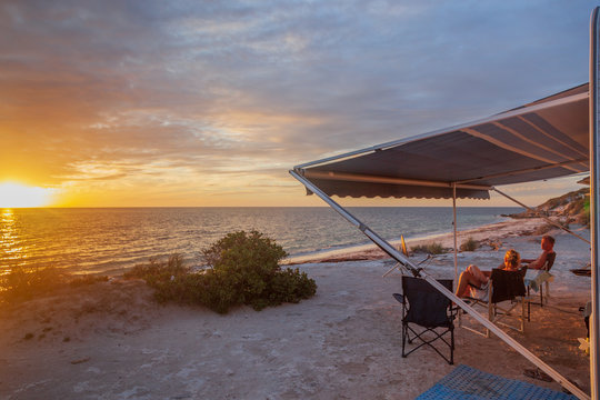 Retired couple sitting under the awning of a of caravan enjoying a wine next the beach with a golden sunset.