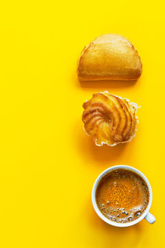 Knolling composition traditional Italian pastry cassatella sweet ravioli with ricotta filling zeppole cup of freshly brewed coffee with foamy crema on bright yellow background. Top view flat lay.