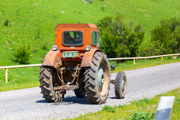 An old tractor is driving down the road