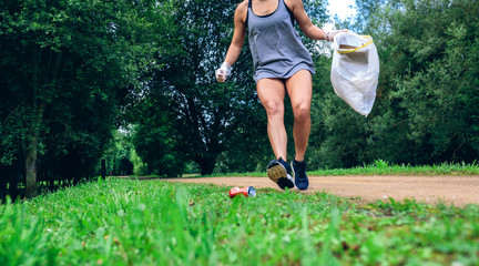 Girl crouching with garbage bag doing plogging outdoors
