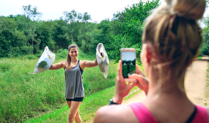 Girl taking a picture of a friend with trash bags after plogging. Selective focus on girl in background