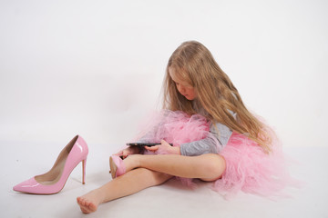 a little caucasian child girl sits and puts mother's high-heeled pink shoes, taking pictures of it all and selfies on her smartphone on white studio background