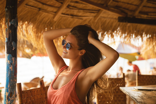 Young woman wearing sunglasses sitting in the beach bar