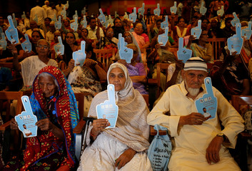 """People, who are scheduled to vote and were invited by the Election Commission of India, attend a felicitation ceremony called """"Shatayu Samman"""", an award given to persons who lived for a century, in Ahmedabad"""