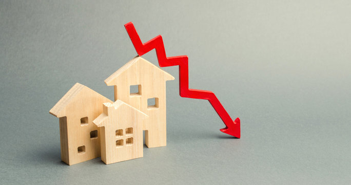 Miniature wooden houses and a red arrow down. The concept of low cost real estate. Lower mortgage interest rates. Falling prices for rental housing and apartments. Reducing demand for home buying