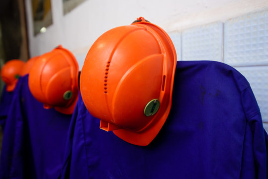 orange-colored mining helmets hang over protective gowns. Working uniform.