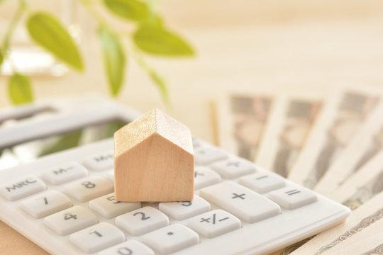 木の家と電卓 紙幣