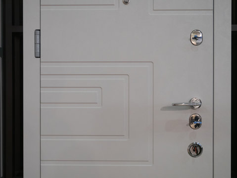 closeup of white entrance modern armored front door with few locks and handle