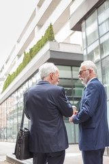 Two senior gray haired businessmen walking down the street, surrounded by modern office buildings. Discussing during informal meeting