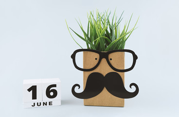 Greeting card with cheerful funny face on paper bag with glasses and mustache, and hair from grass and save date white wooden block calendar for 16st June to celebrate Father's day