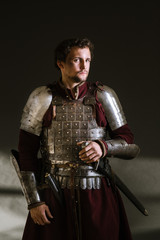 Medieval man knight in armor and weapon on dark background. Portrait of the knight