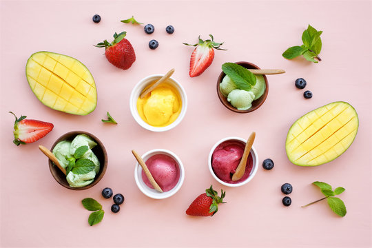 Ice cream set on a light pink background. Berry, pistachio, mango ice cream in bowls