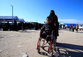 A woman pushes her injured child in a wheelchair at al-Hol displacement camp in Hasaka governorate