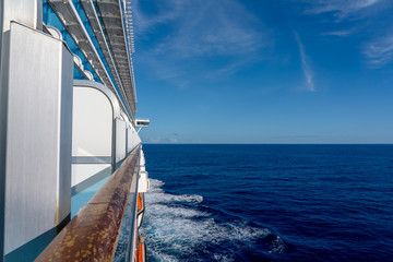 View of the starboard side of a cruise ship on a bright sunny day in the Caribbean Sea.