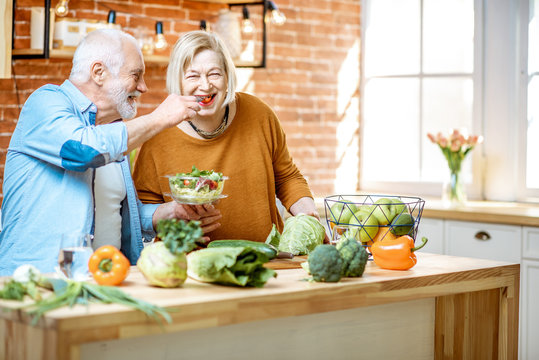 Cheerful senior couple eating salad standing together with healthy food on the kitchen at home. Concept of healthy nutrition in older age