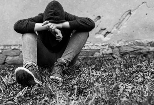 Frustrated teenage boy sitting near a crumbling wall at the correctional institute, focus on the boys shoe, copy space in black and white.