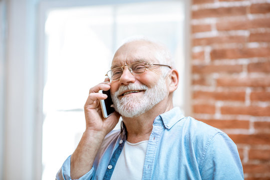 Cheerful senior grandfather talking with phone near the window at home