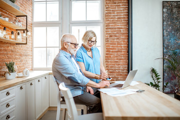 Beautiful senior couple in blue shirts sitting together with laptop on the kitchen at home