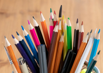 Colorful pencils for creativity in a metal mesh cup on the background of a wooden table.