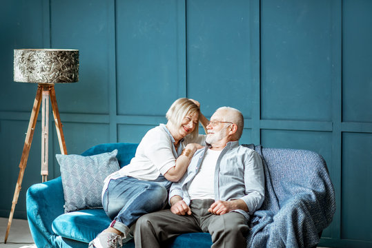 Lovely senior couple dressed casually having fun, sitting together on the couch at home