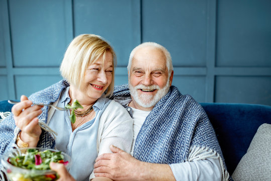 Lovely senior couple eating healthy salad while sitting wrapped with plaid on the couch at home