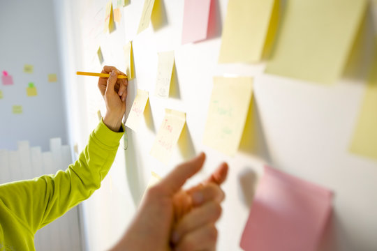 Business people write down an important note, using on the paper stickers post it. The hand of a woman makes a note of the idea, for further development.