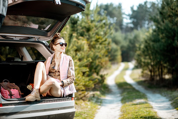Young woman enjoying nature while sitting in the car trunk on a picturesque road in the woods