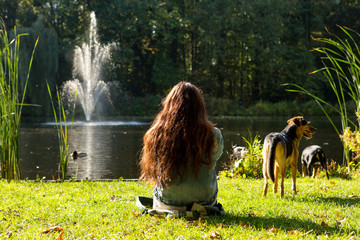 A girl relaxing in the grass at a pond with 2 dogs.