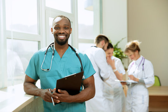 Healthcare people group. Professional african american male doctor posing at hospital office or clinic. Medical technology research institute and doctor staff service concept. Happy smiling models.