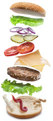 Hamburger ingredients falling down one by one to create a perfect meal. Colorful conceptual picture of burger cooking. Clipping path.
