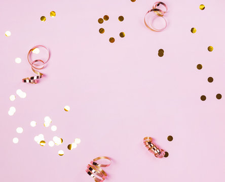 Shiny golden confeti and ribbons on pink background.