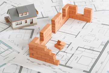 Model house construction with brick on blueprint