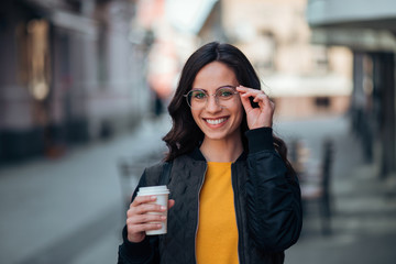 Portrait of smiling young woman holding paper cup, urban scene, city life.