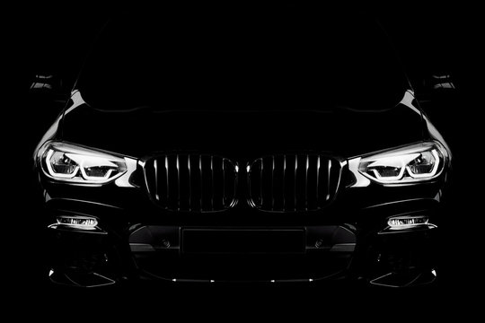 Silhouette of black sports car with headlights on black background.