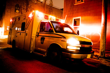 An ambulance car parked on the side street at night Fotomurales