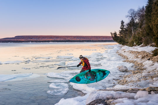 Man gets ready to launch kayak in icy Ontario lake