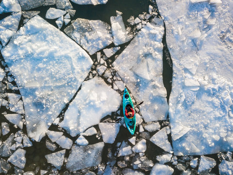 Aerial view of kayaker navigating ice of winter Ontario lake