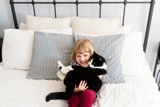 little blonde girl cuddling her big black and white cat on a bed